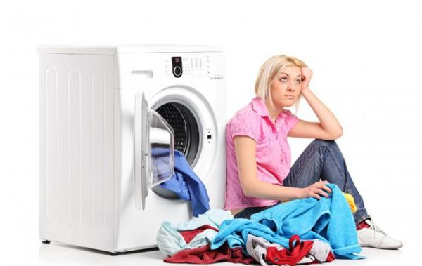 Девушка с бельем возле стиральной машины