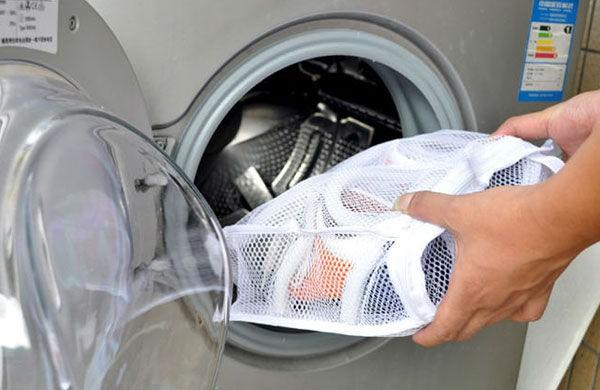 Погружение вещей в специальном мешке в стиральную машину