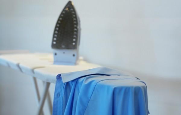 Утюг и рубашка на гладильной доске
