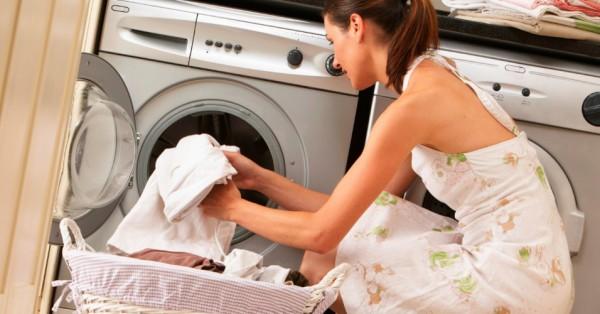 Девушка погружает вещи в стиральную машину