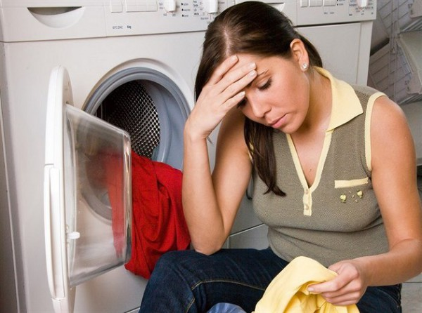 Девушка с вещами рядом со стиральной машины