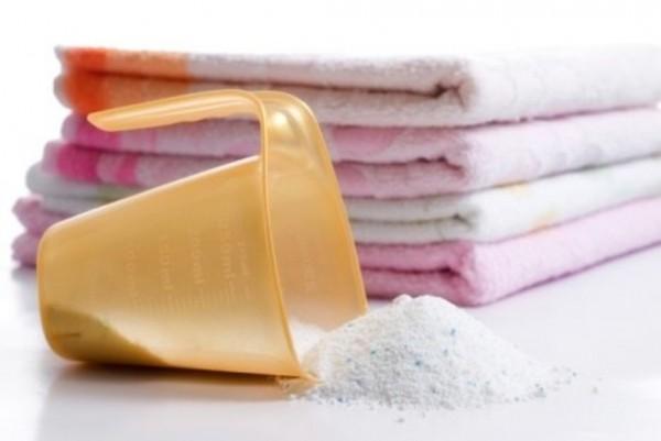 Стиральный порошок и сложенные полотенца