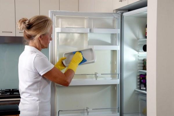 Женщина протирает холодильник