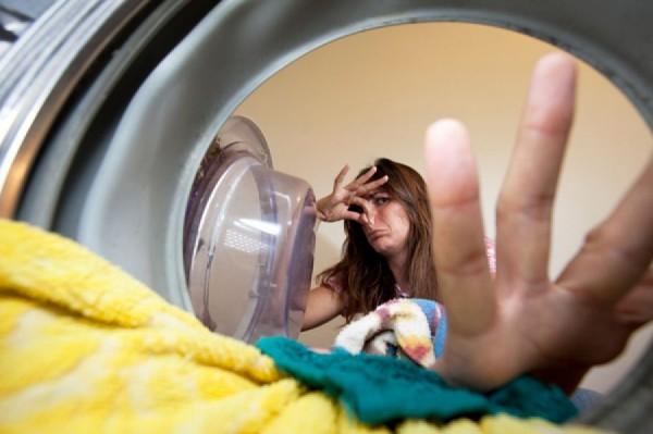 Девушка кладет белье в стиральную машину