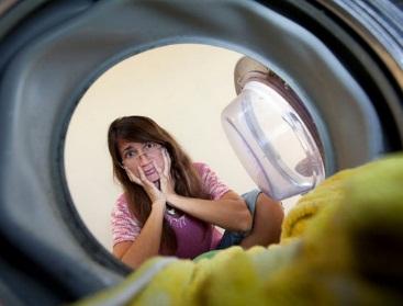 Девушка смотрит в барабан стиральной машины